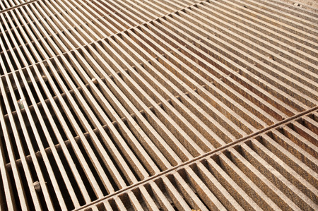 metal grate: The thick rusty metal grate with a rough texture