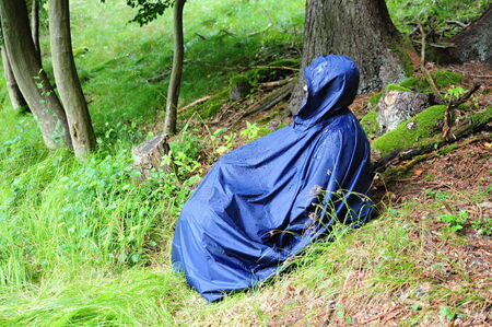 Girl in a raincoat sitting in the rain in the forest photo