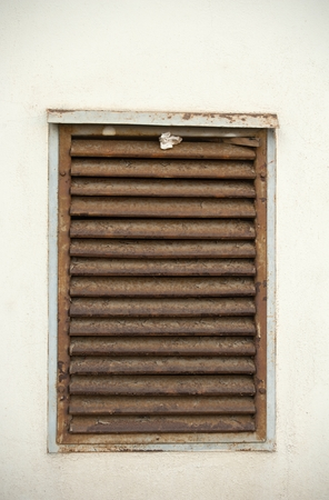 Old ventilation shaft covered with a metal grille on the white wall