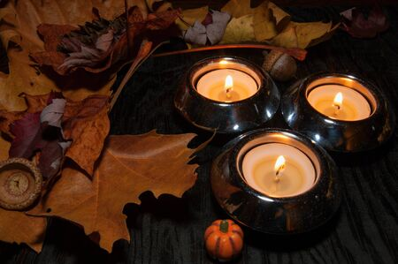 Autumn decoration with dry leaves and burning candles Stock Photo