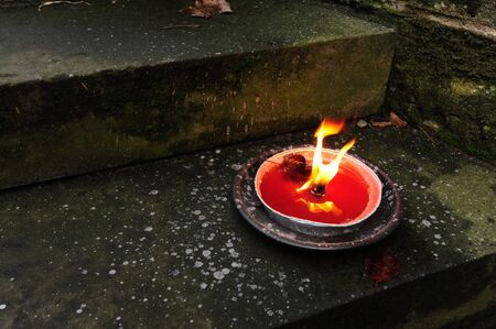 Beautiful red candle burning on the stone steps Stock Photo