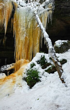 Frozen waterfalls on the rock, orange colored and snow