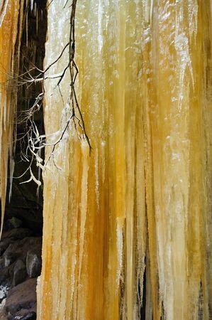 Detail frozen waterfalls on the rock, orange colored