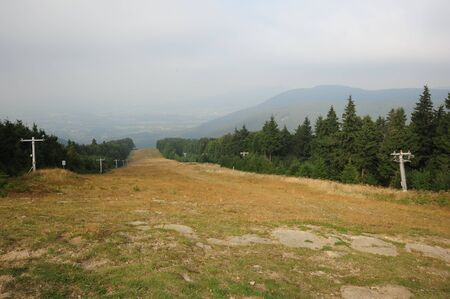 Panorama of beautiful green landscapes in the mist and rain with ski slope