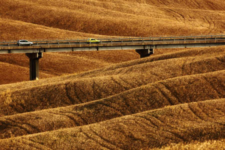 sow: Wavy breown hillocks, sow field, agriculture landscape, bridge with two cars, nature carpet, Tuscany, Italy Stock Photo