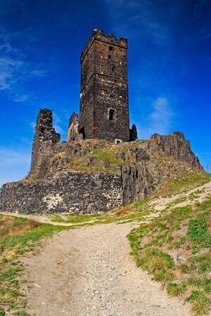 ceske: Hazmburk gothic castle on rocky mountain, with gravel path and blue sky, in Ceske Stredohori, Czech republic.