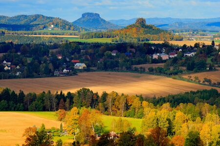 Czech typical autumn landscape. Hills and villages with sun. Morning fall valley of Bohemian Switzerland park. Hills with sun, landscape of Czech Republic, Czech Switzerland, Germany in background.