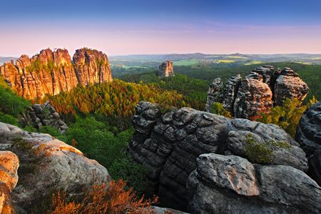 Schrammsteine, beautiful evening view over the sandstone cliff in the deep misty valley in Saxony Switzerland, evening background, the fog is orange due to sunset, star sun on sky, Germany. Last rock light. Archivio Fotografico