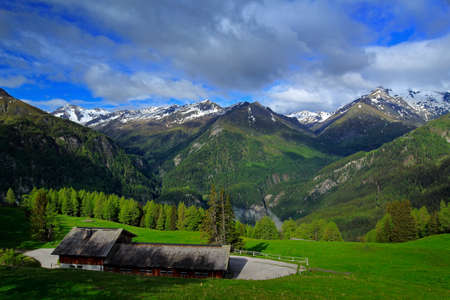Summer green mountains with blue sky and white clouds. Mountains in the Alps. Mountain scenery in summer. Green meadow with mountain in Hohe Tauern Austria. Beautiful summer mountain landscape green. Stock Photo