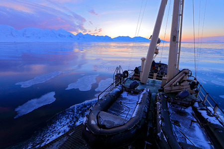 White snowy mountain, blue glacier Svalbard, Norway. Ice in ocean. Iceberg twilight in North pole. Pink clouds, ice floe. Beautiful night landscape. Ship and land of ice.  Boat in winter Arctic.