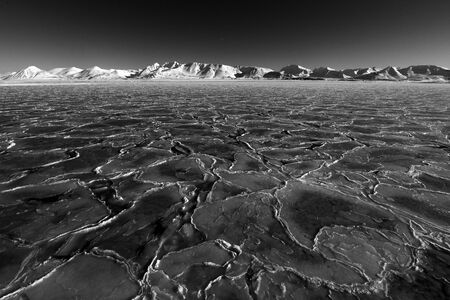 Art view on winter Arctic. White snowy mountain, blue glacier Svalbard, Norway. Ice in ocean. Iceberg in North pole. Global warming, clima change. Beautiful landscape. Black and white. Land of ice.