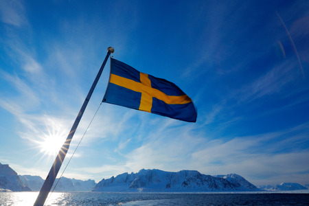 Sweden flag with blue sky. Rocky island with snow. White snowy mountain, blue glacier Iceberg twilight, ocean. Pink clouds with ice floe. Beautiful landscape. Land of ice. Cold blue water nature.