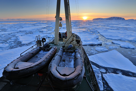 Boat in winter Arctic. White snowy mountain, blue glacier Svalbard, Norway. Ice in ocean. Iceberg twilight in North pole. Pink clouds, ice floe. Beautiful night landscape. Ship and land of ice.