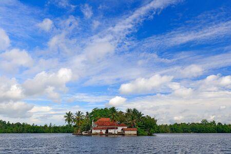 Kothduwa temple, or Koth Duwa Raja Maha Viharaya, Buddhist temple, Madu Ganga clouds with dark blue sky. Bentota river, Sri Lanka. Summer landscape, island with church. Mangrove trees in the water.   版權商用圖片