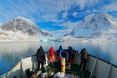 Holiday travel in Arctic, Svalbard, Norway. People on the boat. Winter mountain with snow, blue glacier ice with sea in the foreground. Blue sky with white clouds. Snowy hill in ocean. Travel in sea.