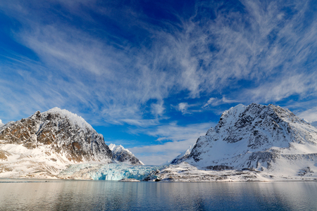 Blue sky with ice floe. Beautiful landscape. Cold sea  water. Land of ice. Travelling in Arctic Norway. White snowy mountain, blue glacier Svalbard, Norway. Ice in ocean. Iceberg in North pole.