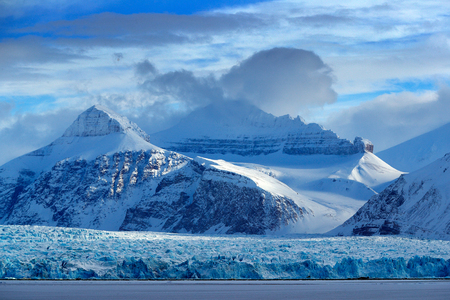 Beautiful landscape. Cold sea water. Land of ice. Travelling in Arctic Norway. White snowy mountain, blue glacier Svalbard, Norway. Ice in ocean. Iceberg in North pole. Blue sky with white ice floe.