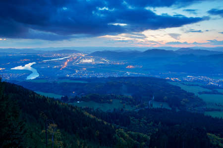 Zilina town in the naght from Mala Fatra mountain. Factory with light. View of the evenig city from the mountains in Slovakia. Mountain forest with storm clouds on sky. Sunset in Slovakia, Vah river.