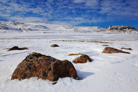 Snowy winter scene from Iceland. White landscape with dark stone and blue with white clouds. Clear day with snow ice lake. Snowy mountain in the Iceland, North of Europe.