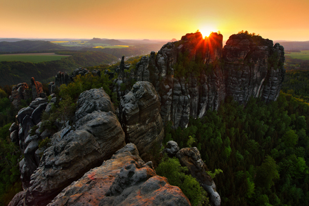 Schrammsteine, beautiful evening view over sandstone cliff into deep misty valley in Saxony Switzerland, foggy background, the fog is orange due to sunset, star sun on sky, Germany.