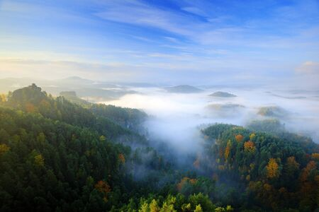 Czech typical morning autumn landscape. Hills and villages with foggy sky. Morning fall valley of Bohemian Switzerland park. Hills with fog, landscape of Czech Republic, Ceske Svycarsko, wild Europe.