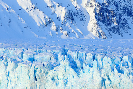 Blue ice and mountain. Winter Arctic. White snowy mountain, blue glacier Svalbard, Norway. Ice in ocean. Iceberg twilight in North pole. Glacier, iceberg in ocean. Beautiful landscape. Land of ice. Stock Photo