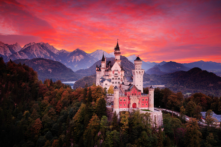 Red sky evening with castle. Beautiful sunset view of the Neuschwanstein fairy tale castle, bloody clouds with autumn colours in trees, twilight night, Bavarian Alps, Bavaria, Germany. Travel Europe.