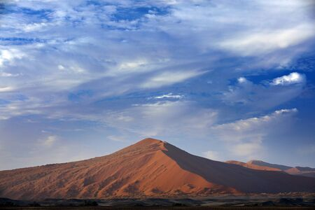 Namibia landscape. Big orange dune with blue sky and clouds, Sossusvlei, Namib desert, Namibia, Southern Africa. Red sand, biggest dune in the world. Travelling in Africa.