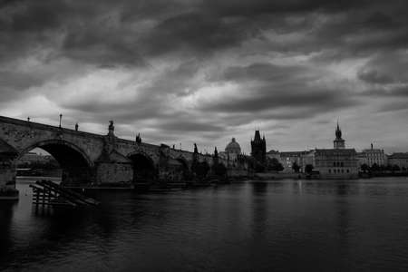 Prague, black and white art photo. Charles Bridge are the symbols of Czech capital, built in medieval times. Misty morning with storm clouds. Traveling in the Europe town. 스톡 콘텐츠