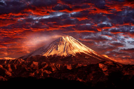 Volcano Fuji during beautiful sunset, red clouds on the sky. Active hill with eruption, twilight in Japan. Mount Fuji, San, orange evening in Asia landscape. Volcan traveling in Japan.