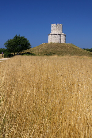 small field: Little old church on the hill above the small field of yellow grass Stock Photo