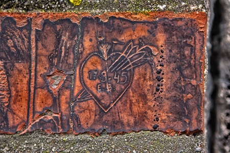 defaced: Heart with date engraved in the old wall brick