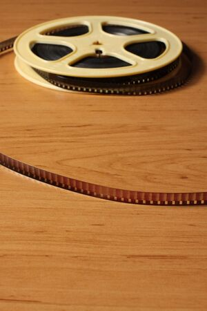 millimeter: Reel with eitght millimeter film on the wooden table