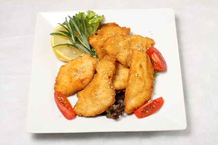 gold table cloth: Fried turkey steak with tomatoes and lemon Stock Photo