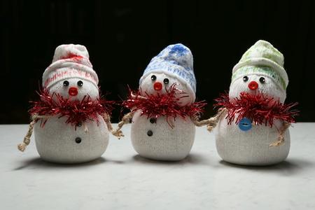 nariz roja: Tres caseras mu�ecos de nieve textiles juguete por el fondo negro Foto de archivo