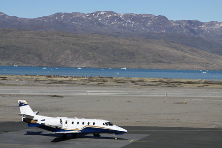 private airplane: Single private airplane standing on the ramp near the sea shore and mountains Stock Photo