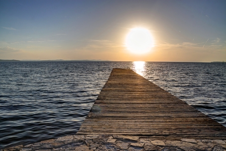 the setting sun: Wooden pier into the sea while sun is setting