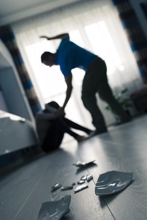 paliza: El hombre golpeando a la mujer en el piso
