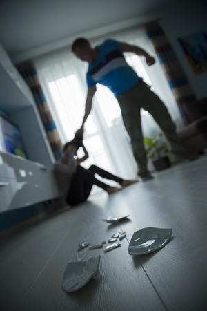 El hombre golpeando a la mujer en el suelo