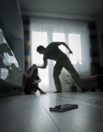 battered woman: Man yelling at woman on the floor
