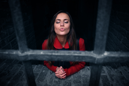 culpable: beautiful girl in a red jail for sending a kiss