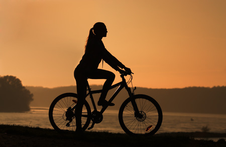 Young girl sitting on the bike by the river at sunset, photo