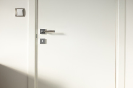 handle: White wooden door frames door light switch Stock Photo