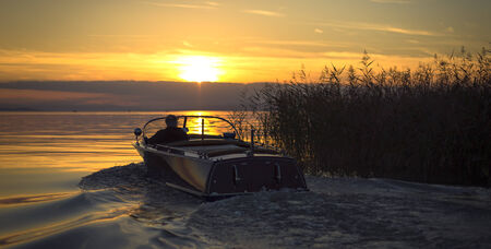 reeds and motor boat on the lake at sunset photo