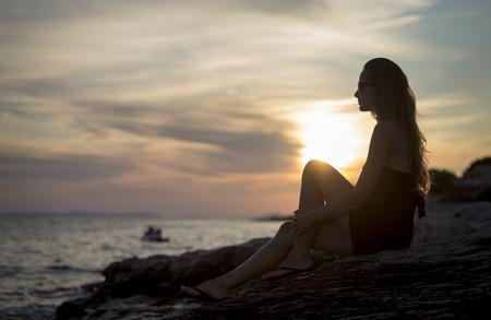 pretty girl sitting on seashore at sunset Stock Photo
