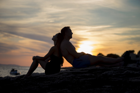 couple in love by the sea in the sunset photo