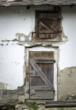 dilapidated wall: door to the pigsty with dilapidated wall to rural areas Stock Photo
