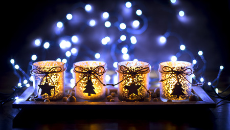 Advent, four candles decorated Christmas tree on a background of lights Stock Photo