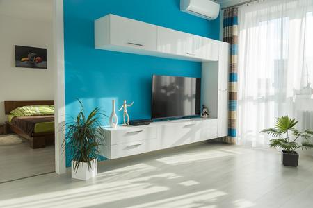 Moderne zonnige woonkamer met tv en uitzicht op de slaapkamer