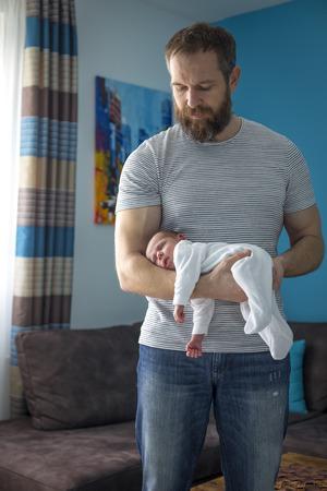 hand position: Mensual beb� durmiendo en el brazo de la mano de su padre, posici�n para ayudar a los c�licos Foto de archivo